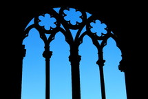 Silhouette of cathedral window frame against a bright blue sky
