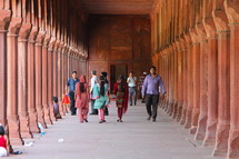 People walking through the covered walkway surrounding the Taj Mahal