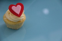 Cupcake decorated with cream cheese, sprinkles and a red St Valentine's heart