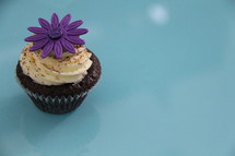 Cupcake decorated with cream cheese, sprinkles and a purple flower against a blue background