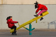 two little girls on a seesaw