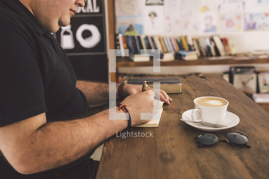 a man writing in a notepad