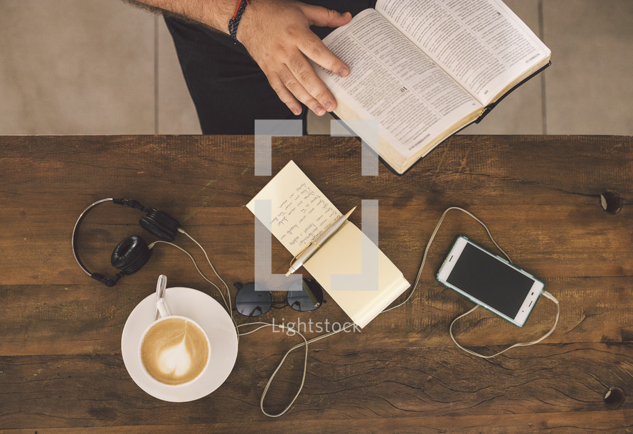 a man writing in a notepad and reading a Bible