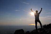 Man with his hands raised in the air in victory and accomplishment standing on top of a mountain