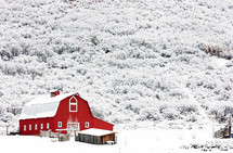 Red barn in snow, with snow-covered hillside in the background.