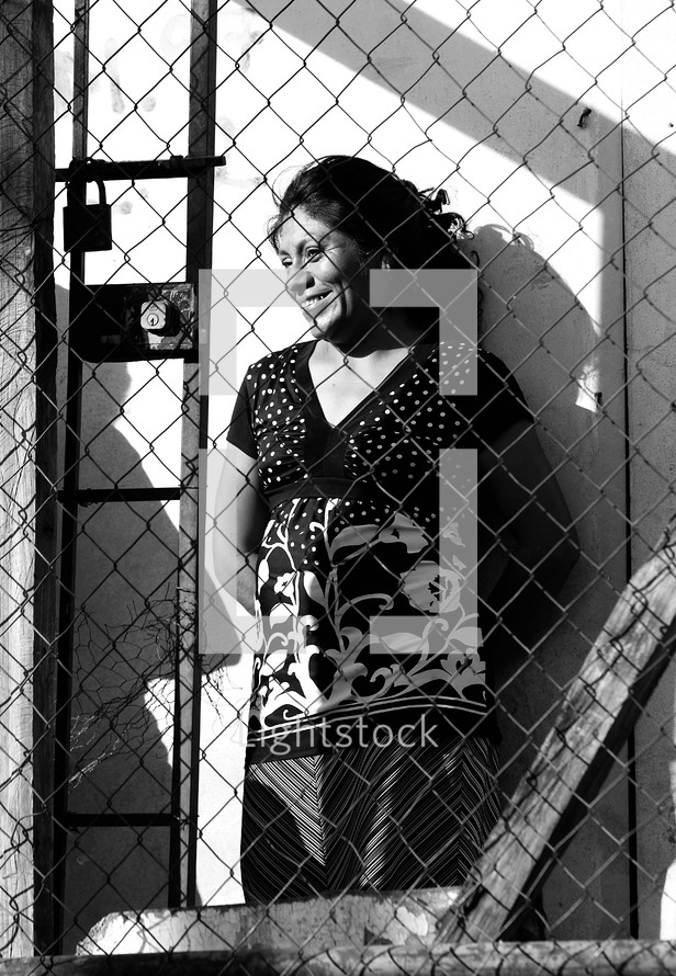 Woman standing behind locked fence