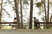 bride and groom sitting apart on benches