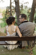 bride and groom sitting on benches outdoors