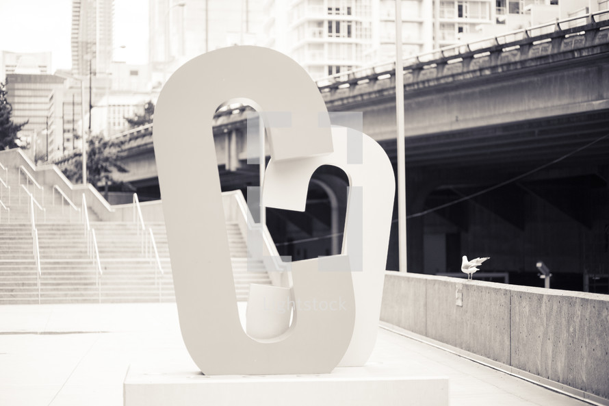 "Letter ""C"" sculpture on the platform of a subway station."