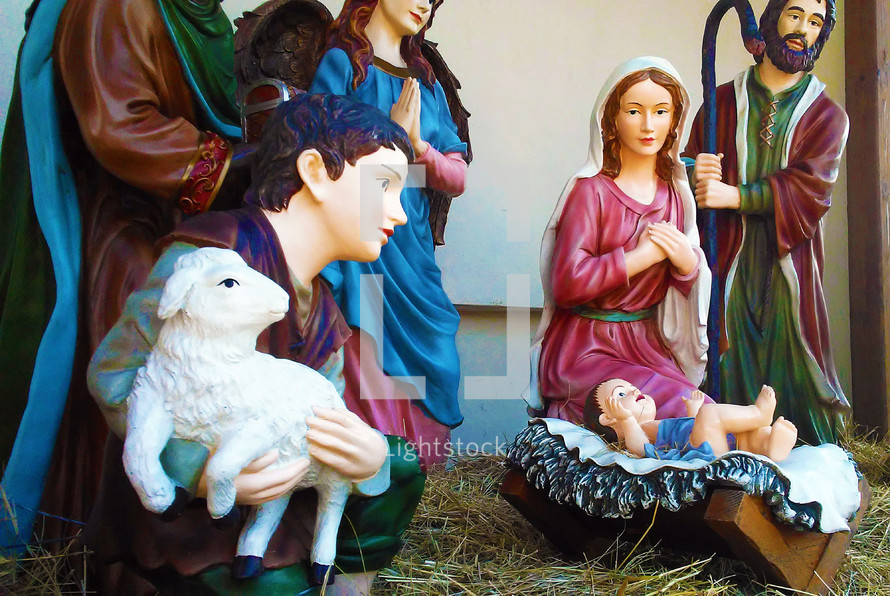 A Nativity scene featuring Baby Jesus born in the manger surrounded by Mary, Joseph, The Wise Men and an Angel glorifying Jesus admiring the child in His innocence and divinity.