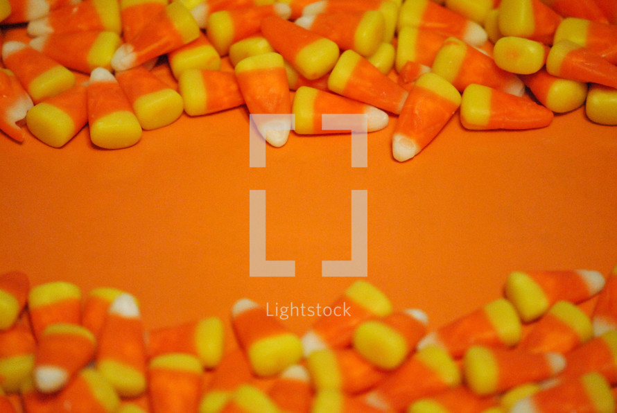 Orange surface with candy corn borders for Halloween or Thanksgiving message.