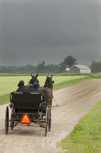 Horses pulling a carriage on a dirt road toward a farmhouse.