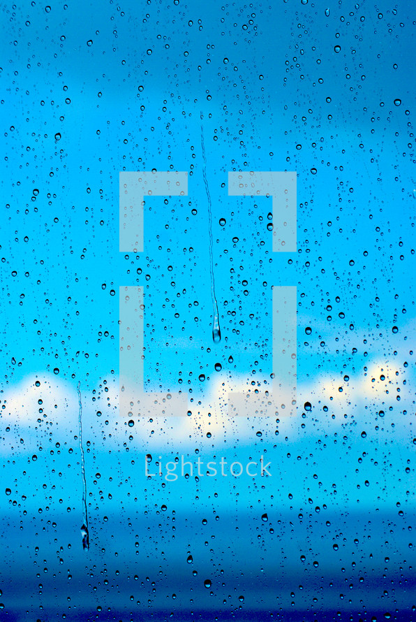 Blue sky and clouds seen through a window covered in raindrops.