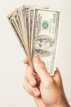 Hand holding fan of paper money.