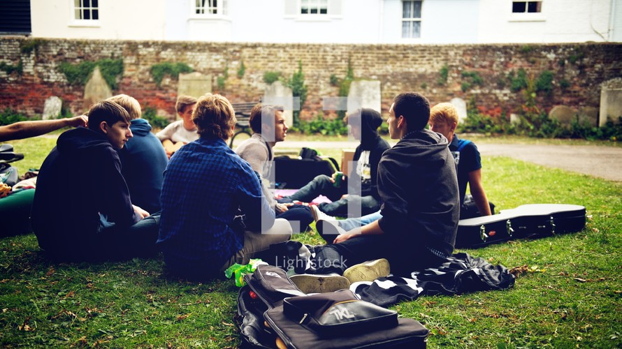 young men sitting in the grass next to guitar cases