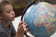 A boy studying a globe.