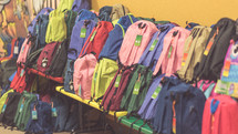 Benches full of colorful backpacks.