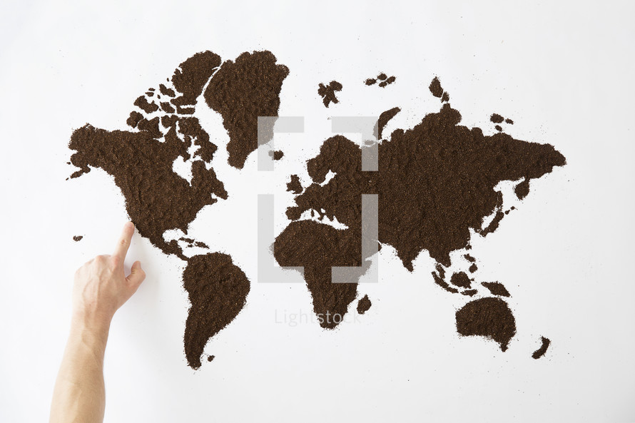 finger pointing to a world map made of dirt.