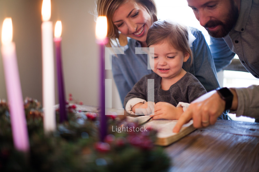 family reading a Bible near an Advent wreath