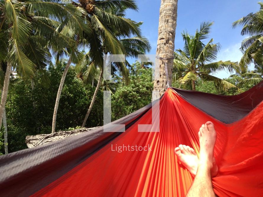 The feet of a man lying in a hammock.