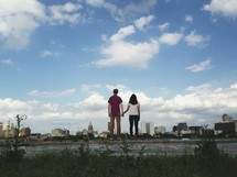 A couple holding hands, enjoying the view.