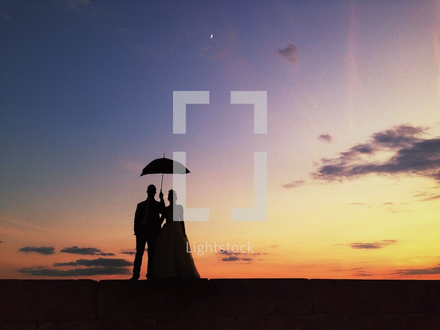 silhouette of a man and woman standing under a parasol.