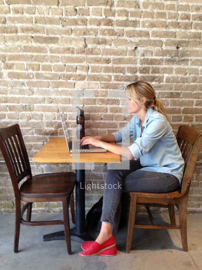 Woman with a laptop sitting in a cafe.