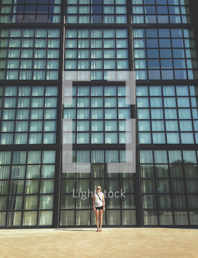 A woman standing in front of a wall of glass windows.