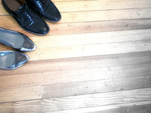 men's and women's dress shoes on a wood floor