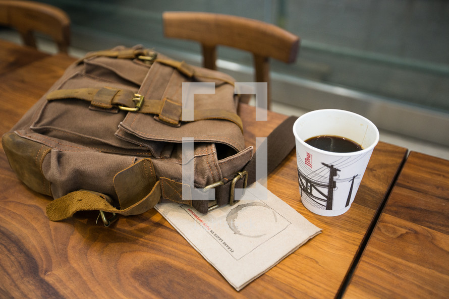 coffee cup and backpack on a wood desk