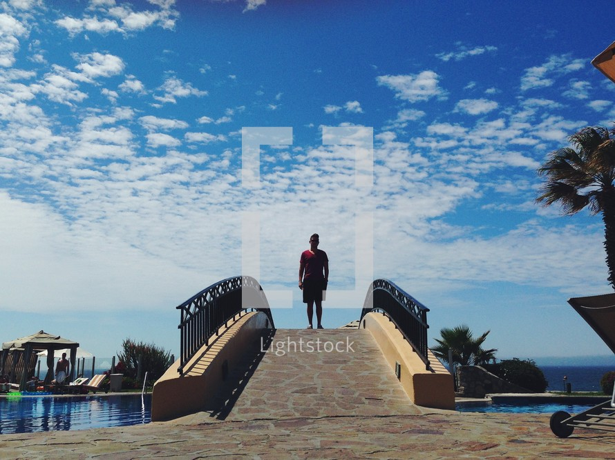 A man standing on a bridge over a swimming pool.
