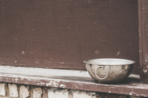 metal bowl in a window sill