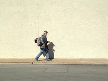 A homeless man walking down a sidewalk.