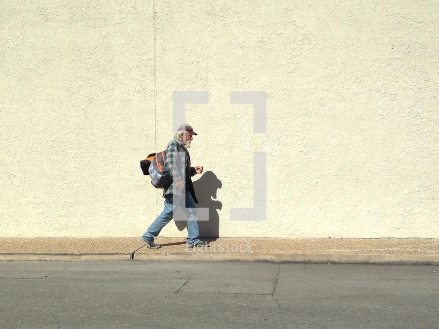 A homeless man walking down a sidewalk.