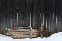 a sled against a wooden fence