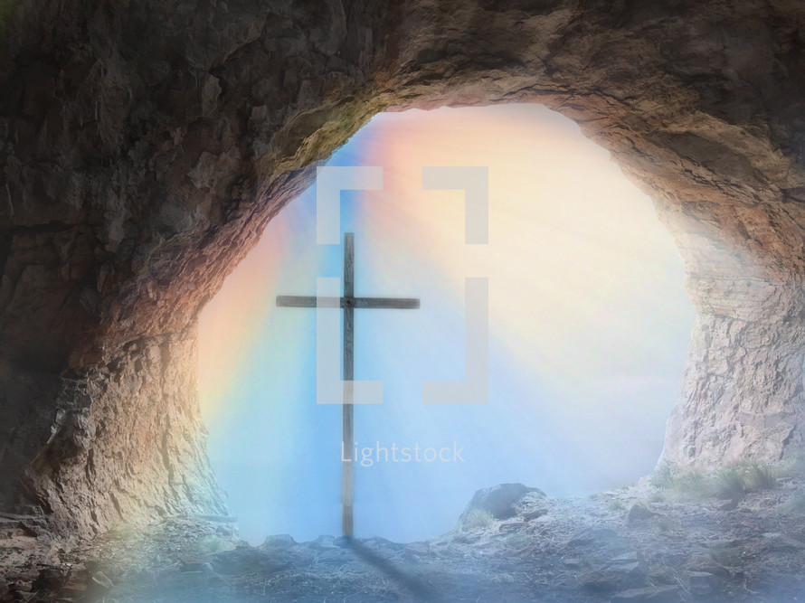 cross and rainbow at the mouth of a cave