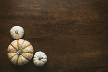 three pumpkins in a corner on a wood table