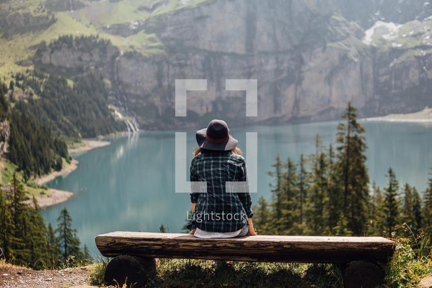 Woman sitting on a bench at a mountain lake