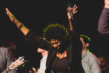 a woman holding a microphone praising God