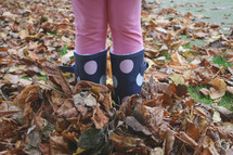 girl with rain boots in fall leaves