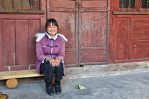 Smiling Chinese woman sitting on a bench in a 'Siheyuan' courtyard residence {Also try search for 'Ethnic Faces'}