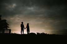 silhouette of a couple holding hands on a shore