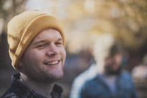 A young man smiling with a yellow beanie on