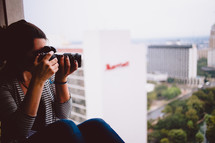 woman with a camera taking a picture while sitting in a window sill