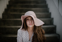a woman in a hat sitting on steps