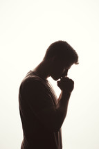 silhouette of a man in prayer