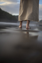 Legs of Jesus standing on a shore
