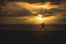 silhouette of a man throwing a frisbee on a beach