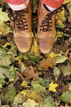 woman's boots standing in fall leaves