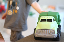 toddler playing with a toy truck